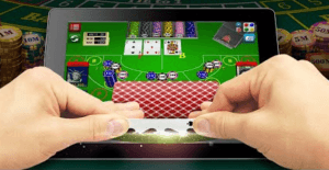 Pair of hands slightly lifting a card in a Baccarat game in an iPad that is placed on top of a Baccarat table