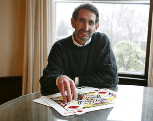 Photo of Bill Kaplan seated in front of a glass table with his hand on top of two big cards - a Jack of Diamonds and Ace of Spades