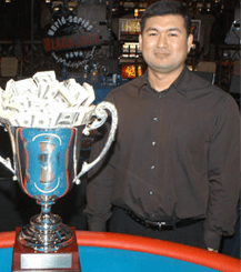 Photo of Mike Aponte standing behind a huge silver trophy filled with cash