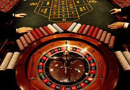 Roulette wheel with two pairs of hands on the betting table