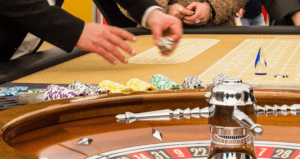 Roulette wheel and a betting table with a pair of hands throwing dice