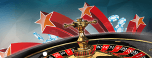 Photo of the top half of a roulette wheel with red stars and blue chips over and behind it