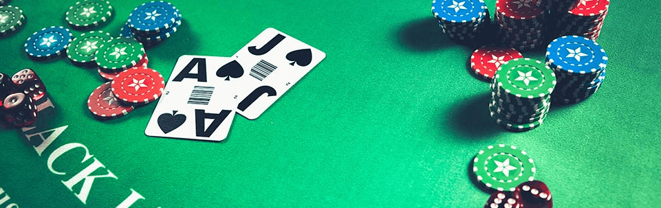 Blackjack table with three red dices, Ace and Jack of Spades cards, and stacks of chips on both sides