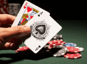 Photo of a hand holding a King of Hearts and Ace of Spades with casino chips on a table