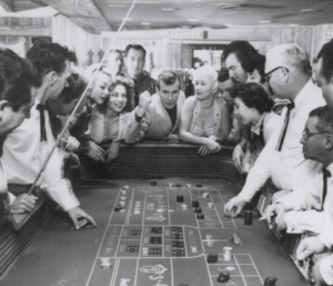 Vintage photo of people gathered around a casino table playing craps