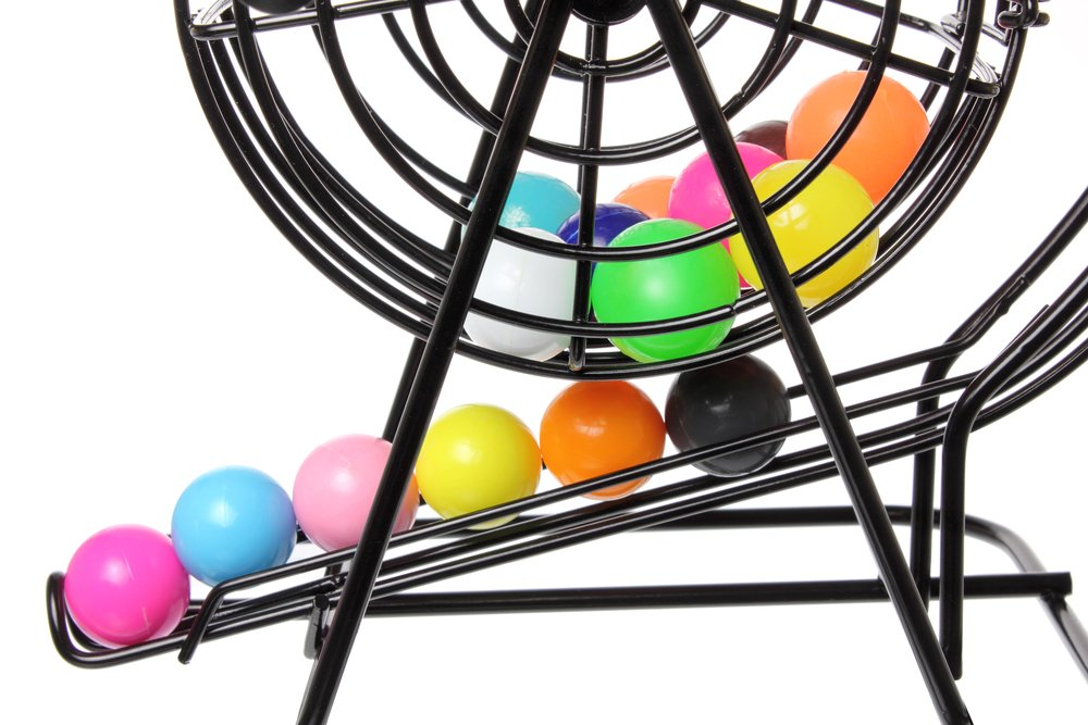Colorful Bingo balls rolling out of a black Bingo Cage